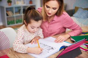 Szkoła zamknięta. Dziewczynka podopieką mamy uczy się pisać - zdjęcie ilustracyjne